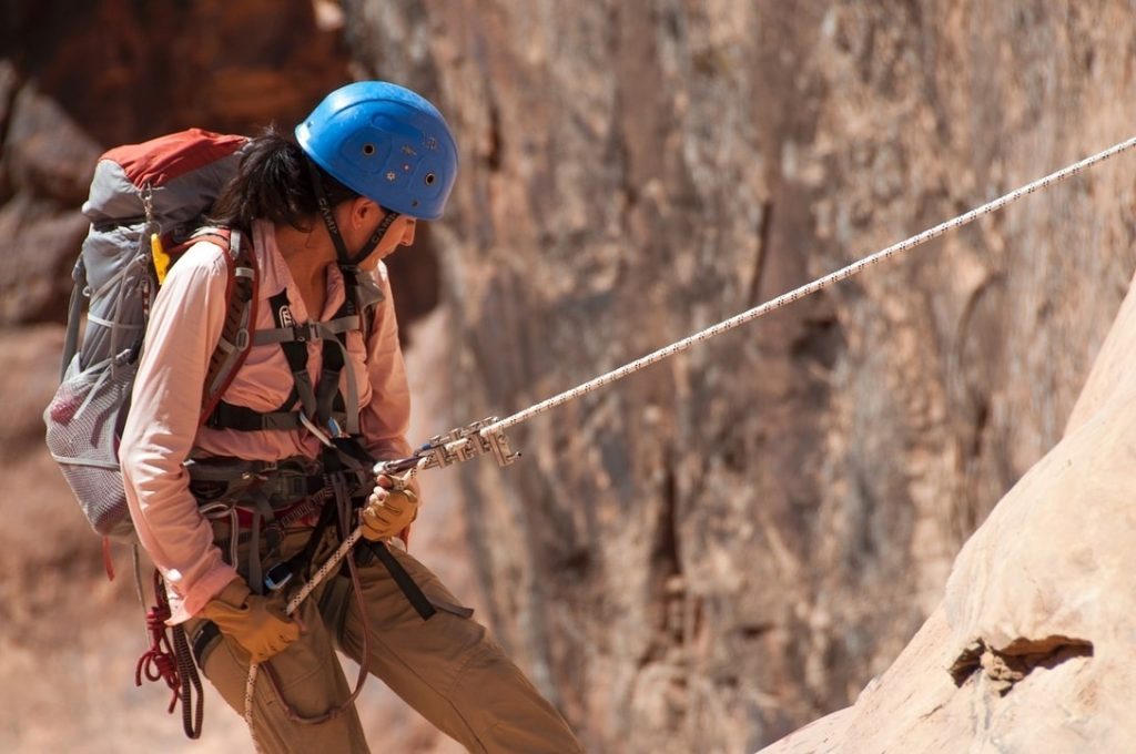 Female climber repelling down a rock face