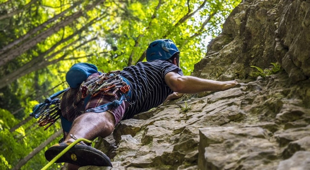 Male climber scaling a rock face in front of green trees