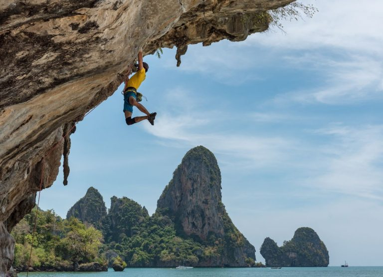 man hanging from a cliff over water