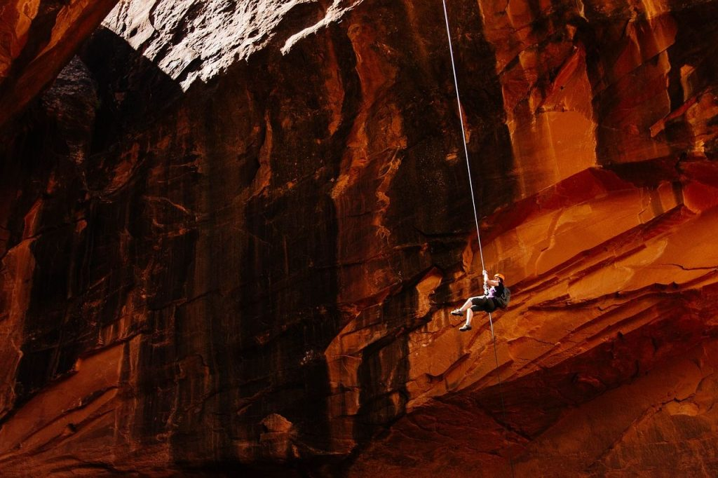 person rapelling from a sheer, red cliff face