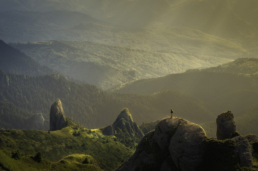 Soft light over a green valley with a hiker standing on a peak
