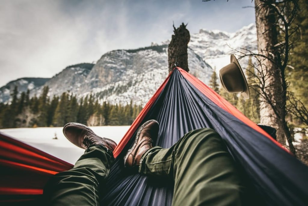legs of person in a hammock with mountain view
