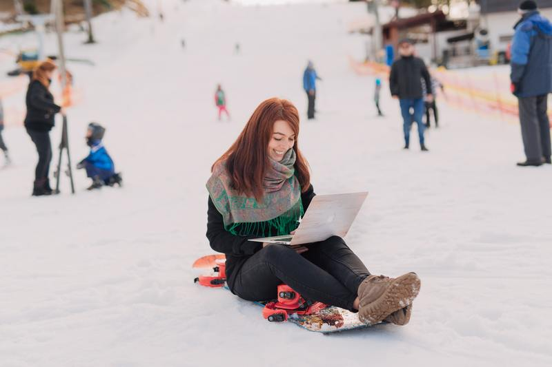 Snowboarder sitting on a board while holding a latop