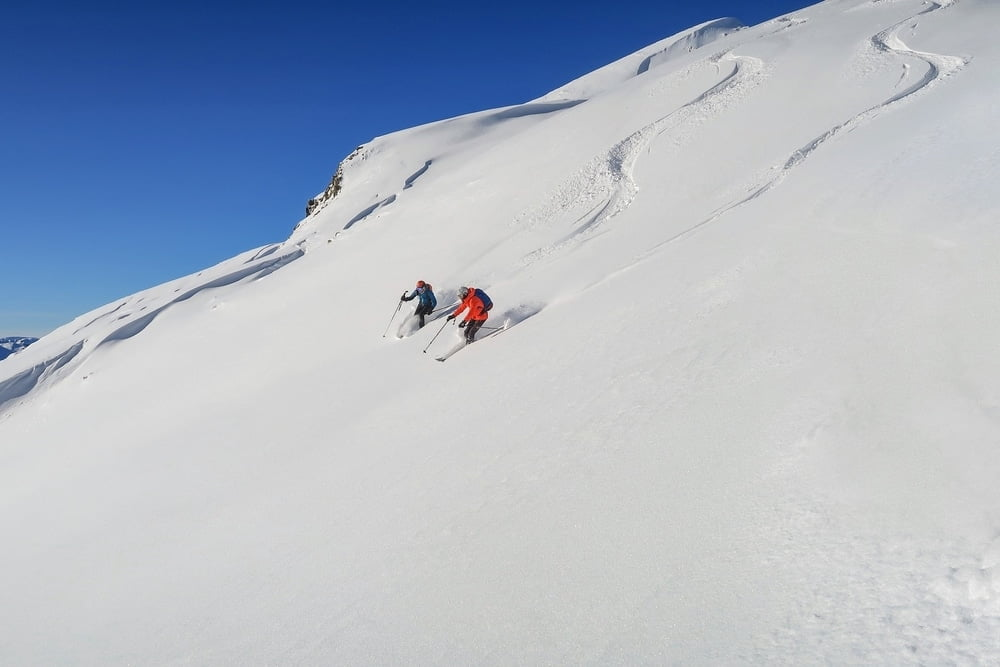 Two people skiing at Alyeska, the resort with the most snow