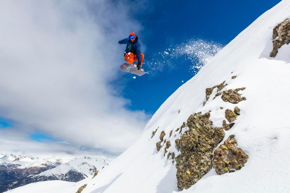 A snowboarder in the air doing an indie grab at the ski resort with the most snow in Wyoming