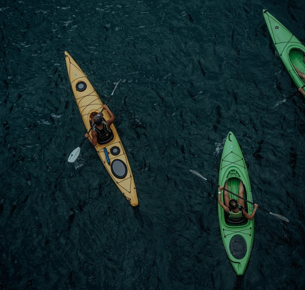 People paddling kayaks of different widths