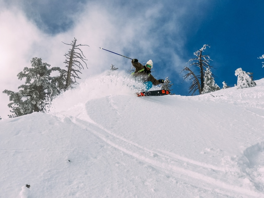 A skier doing a bank turn in deep powder at Sugar Bowl, a ski resort that gets the most snow in California