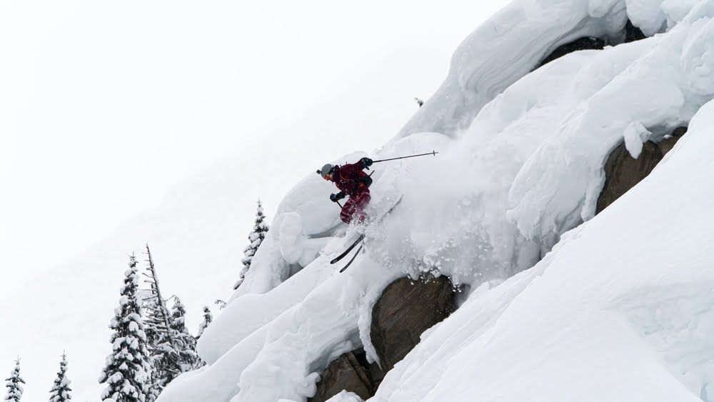 Skier riding in powder at the ski resort with the most snow in British Columbia
