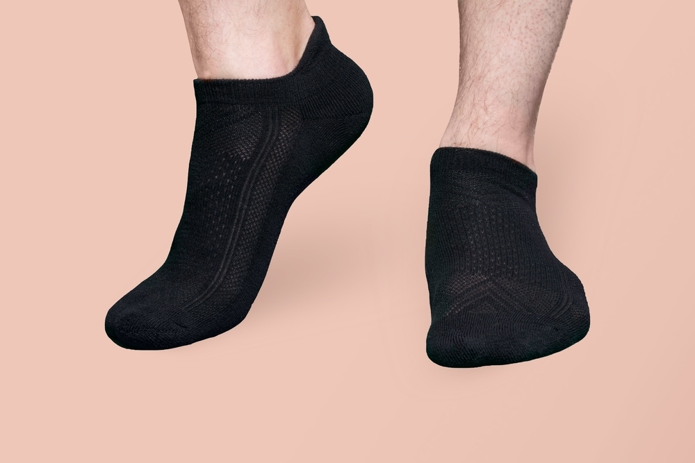 A person wearing black socks that can be used to break in climbing shoes
