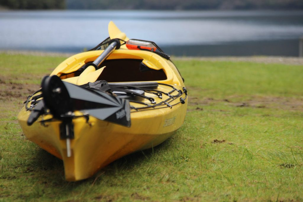 yellow kayak ready to be launched next to lake