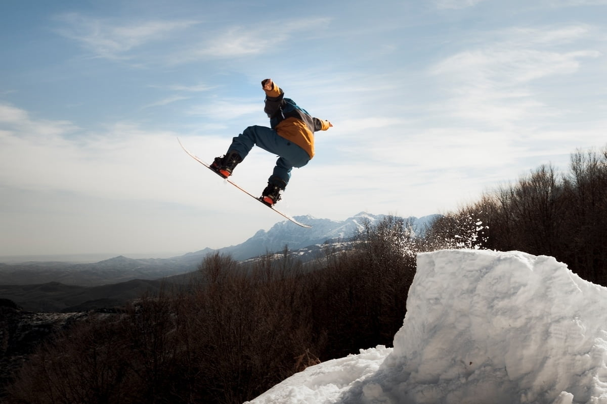 Snowboard trick after coming from the snow ramp