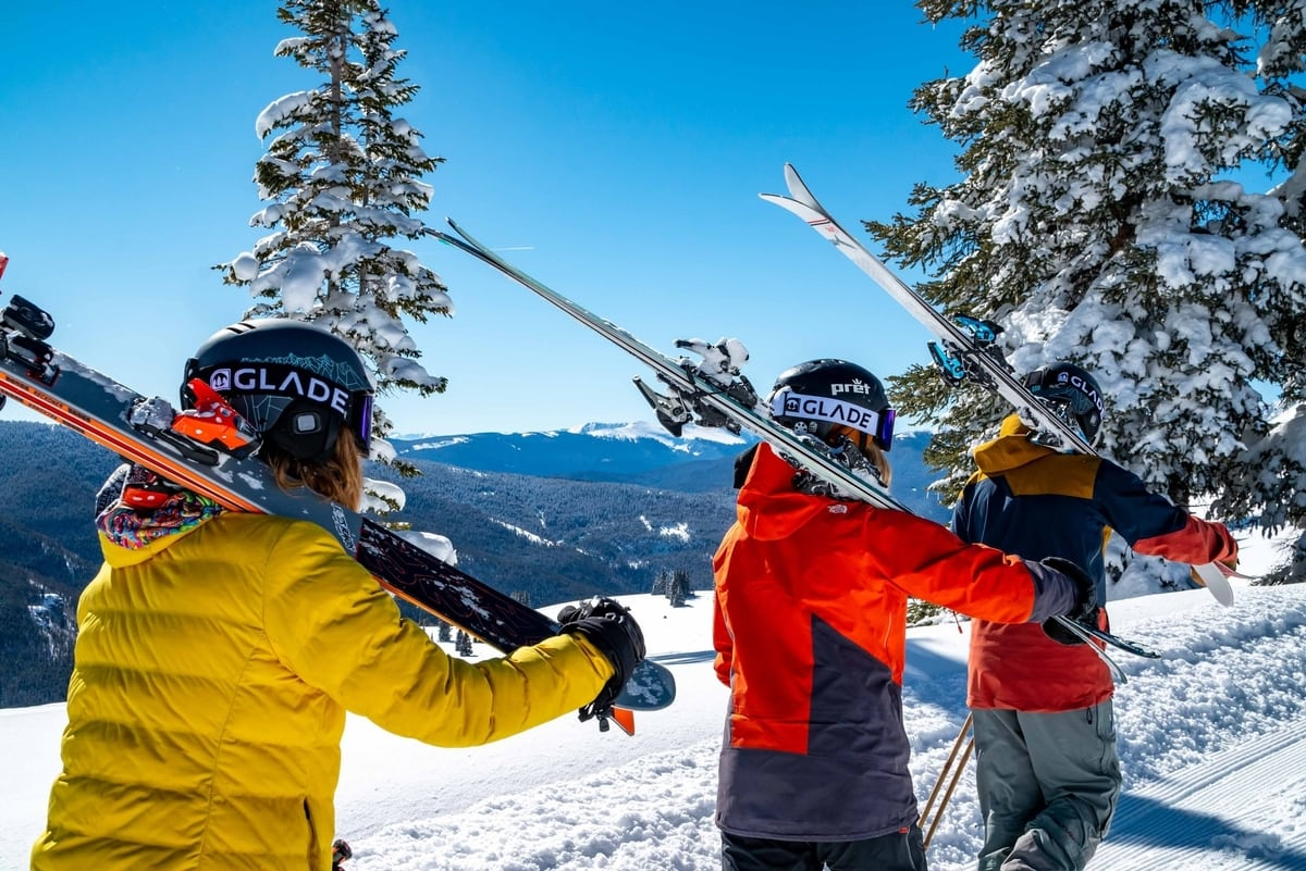 Three people carrying their skis