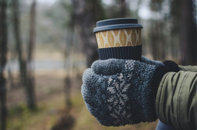 A pair of hands in woolly winter gloves , holding a cup of coffee
