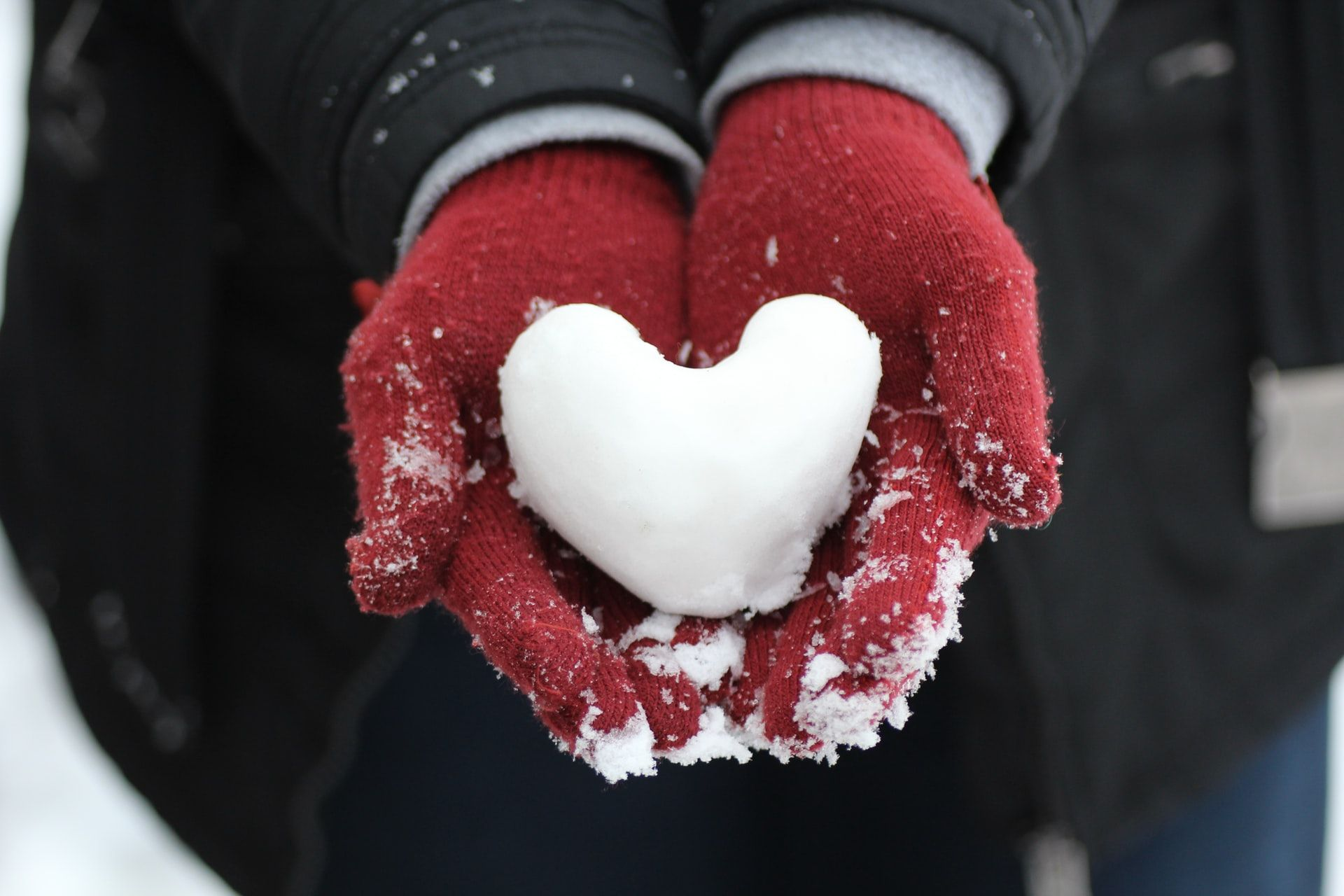 A woman cupping her hands in a red pair of winter gloves and holding a small snowball