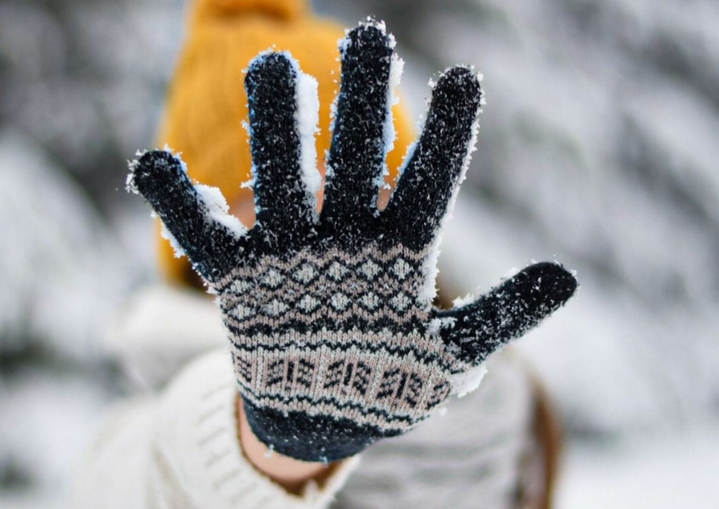 A child holding their hand out to the camera, wearing a snow-covered glove