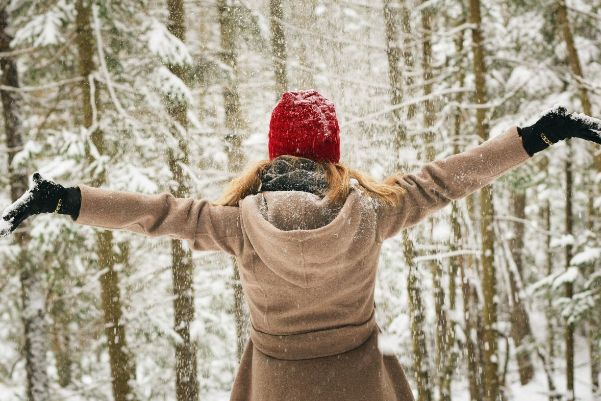 A woman wearing gloves, a winter hat, and some gloves in a snowy forest