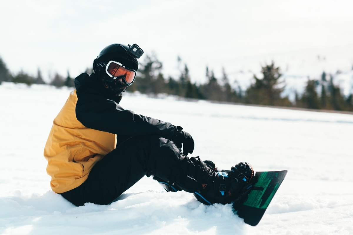 man sitting on snow with feet in board