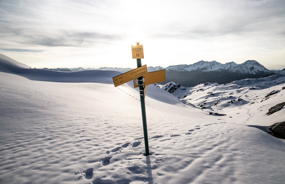 directional signs on a pole in the snow on a slope