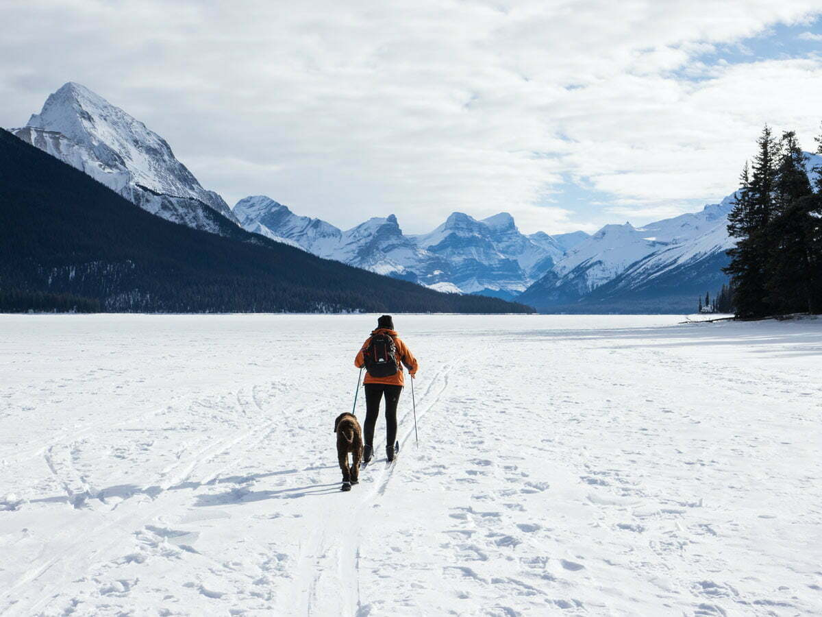 woman snow shoeing outdoors with dog