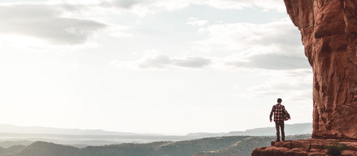 Man standing on a cliff looking at the sky