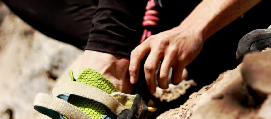 A person putting their foot into a climbing shoe