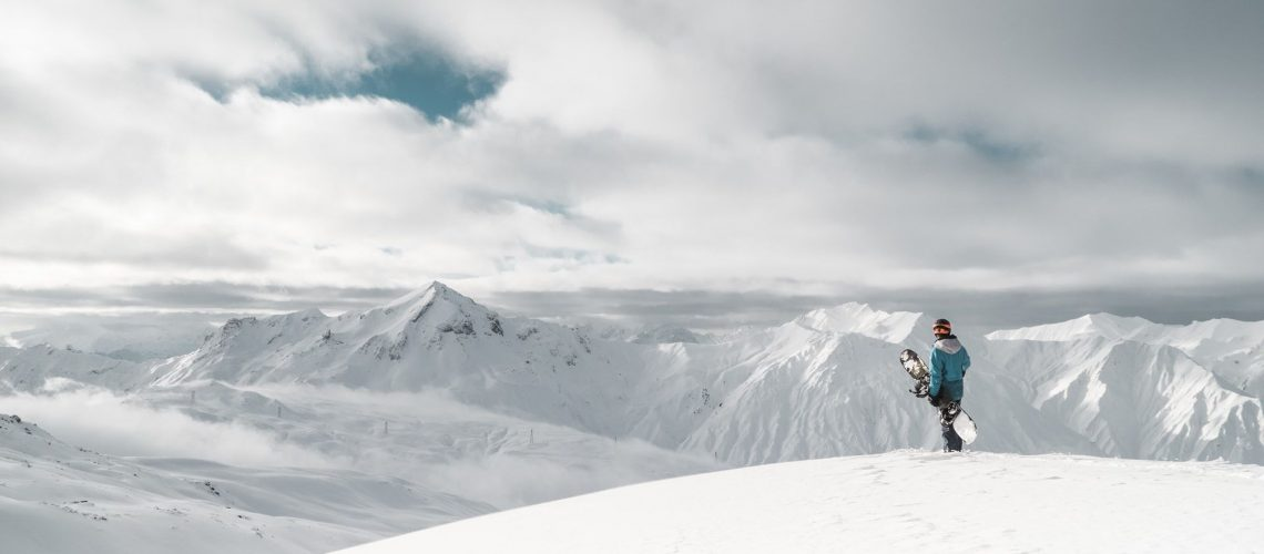 Snowbarder standing on a mountain looking out across a valley