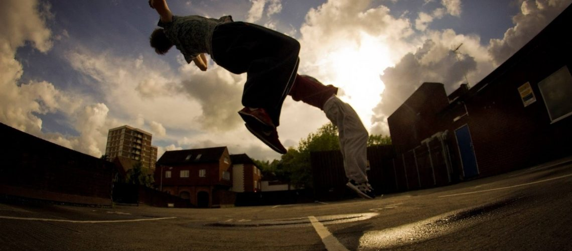 Parkour practitioners perfirming backflips side by side, with dramatic cloudy sky in the background