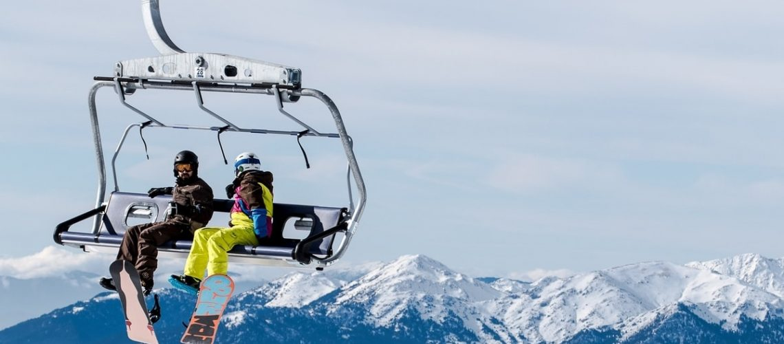 two skiers on a lifted chair lift